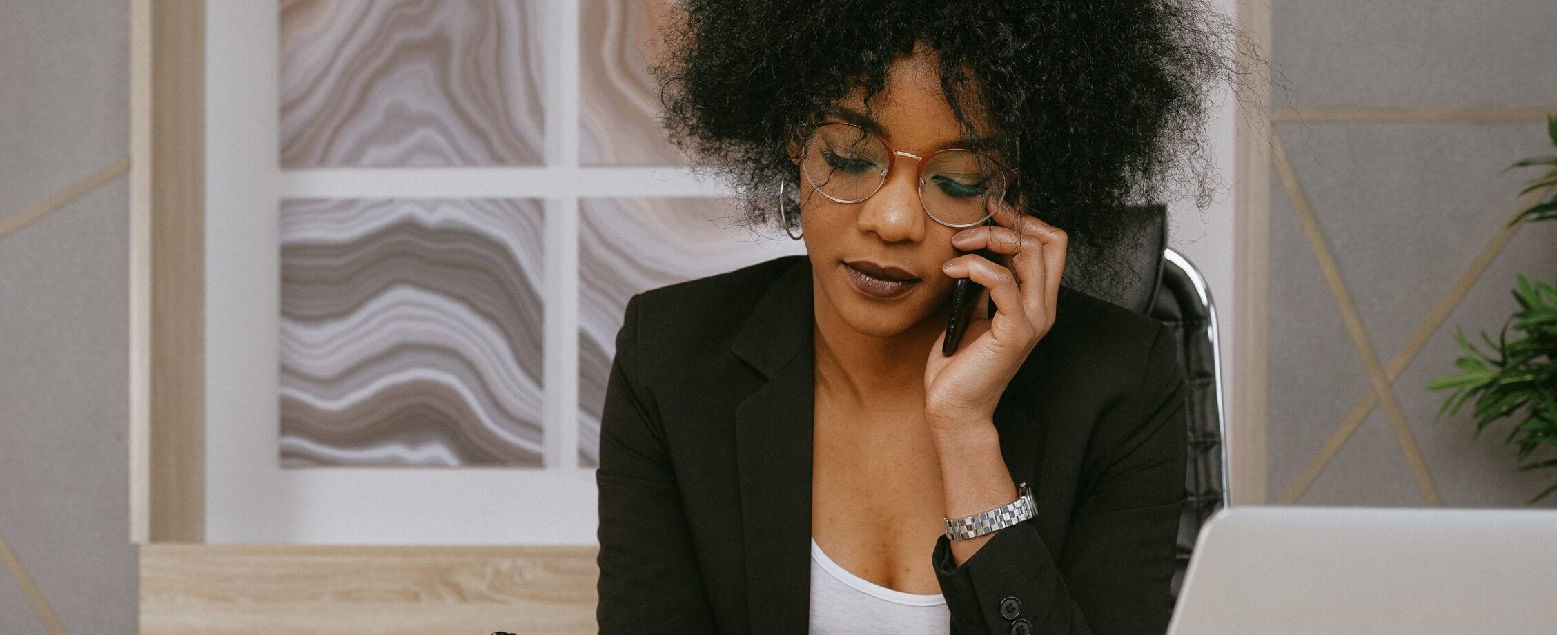 Woman In Black Blazer Sitting By The Table While Using Phone